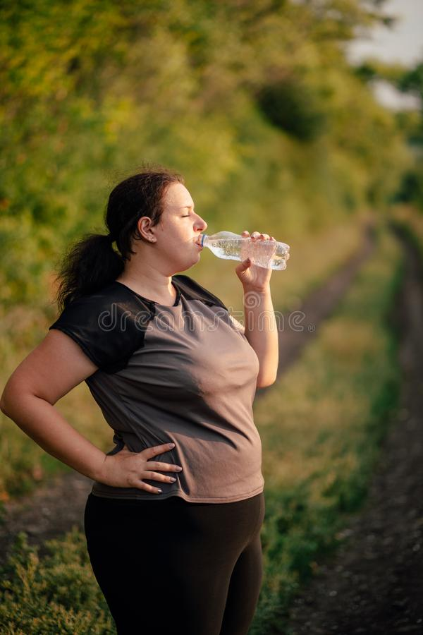 Overweight woman drinking water after workout royalty free stock images