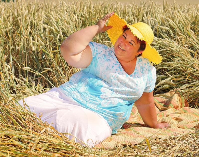 Overweight woman enjoying life during summer vacations. Happy obese farmer relaxing on wheat field. Healthy lifestyle concept royalty free stock photography