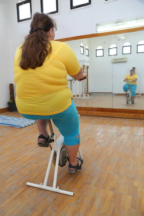 Overweight woman exercising on bike simulator stock photos