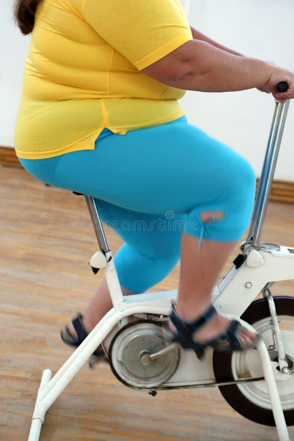 Overweight woman exercising on bike simulator stock image