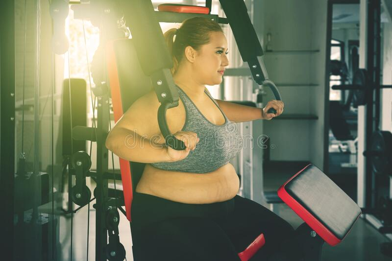 Overweight woman exercising with a fitness machine stock image