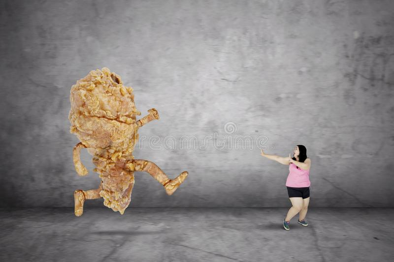 Overweight woman escaping from a fried chicken stock photo