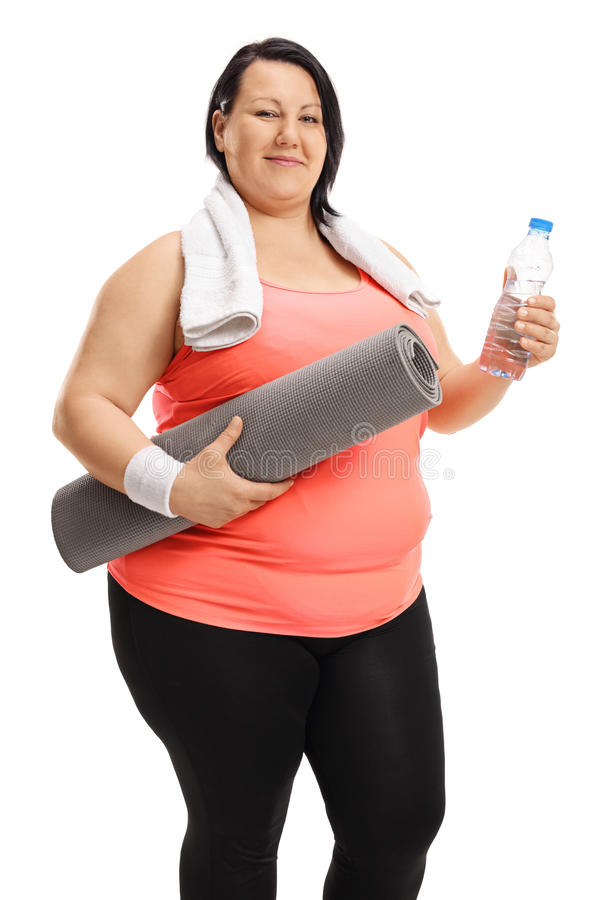 Overweight woman holding exercising mat and bottle of water. Overweight woman holding an exercising mat and a bottle of water isolated on white background stock photos