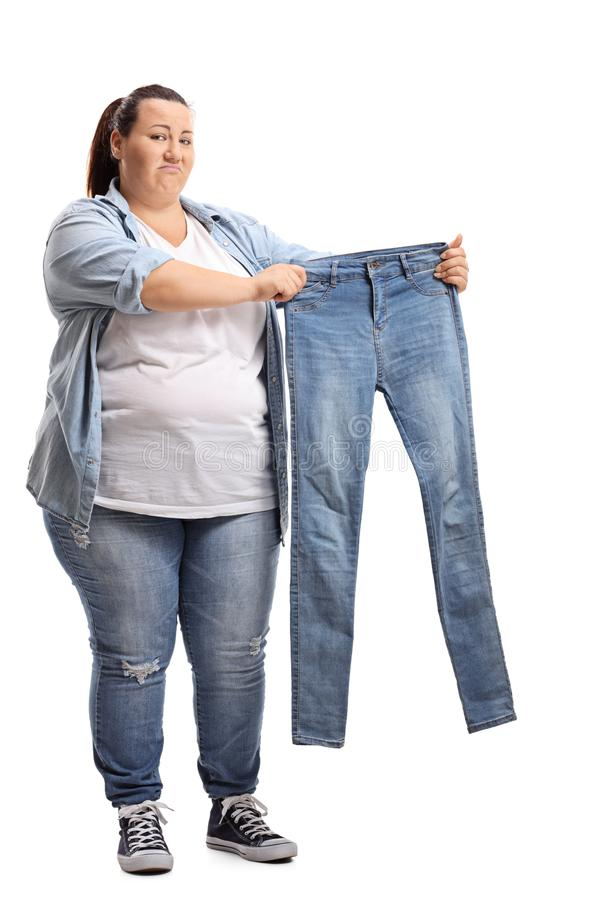 Overweight woman holding a pair of small jeans royalty free stock photos
