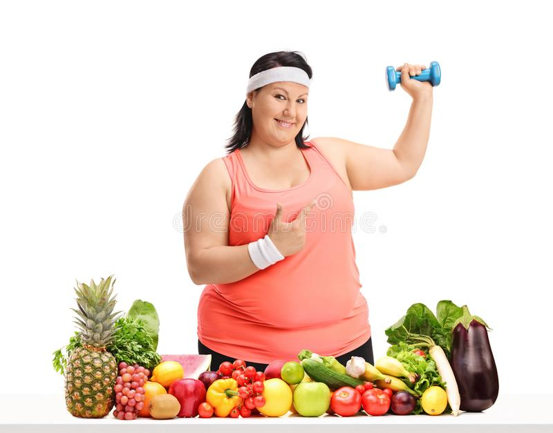 Overweight woman holding a small dumbbell and pointing behind a. Table with fruit and vegetables isolated on white background royalty free stock images