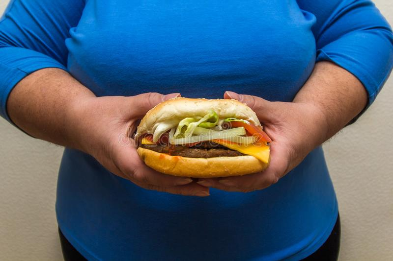 Overweight woman holds hamburger. Overweight woman wearing blue shirt holds hamburger royalty free stock images
