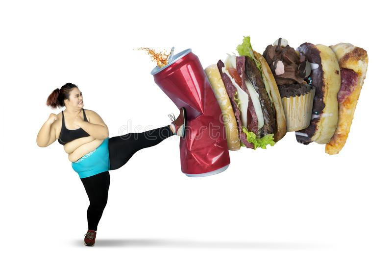 Overweight woman kicking soft drink and fast foods royalty free stock images