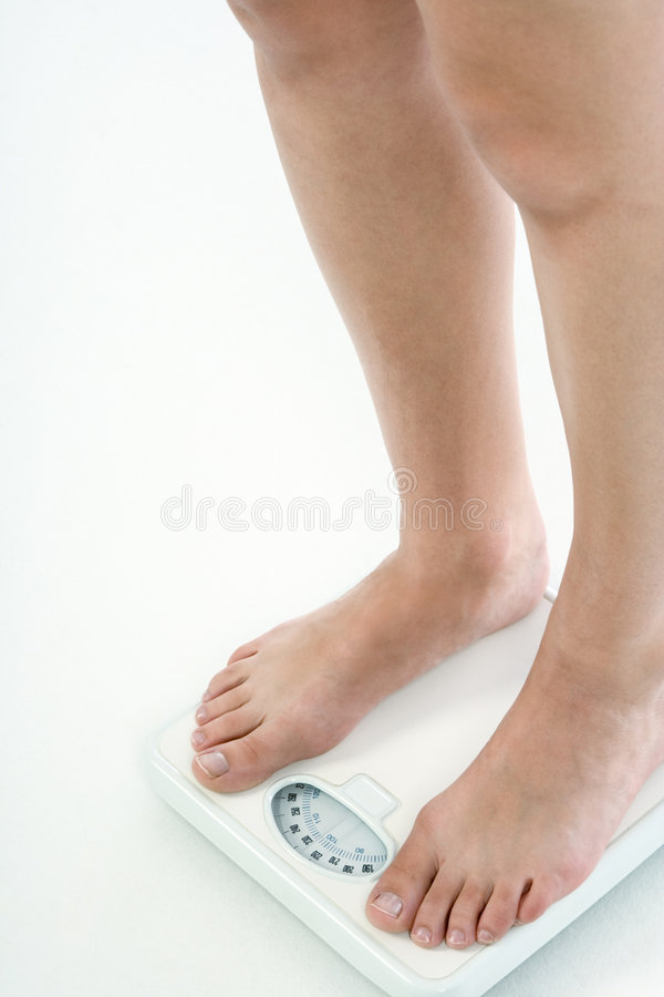 Overweight woman legs standing on bathroom scales royalty free stock images