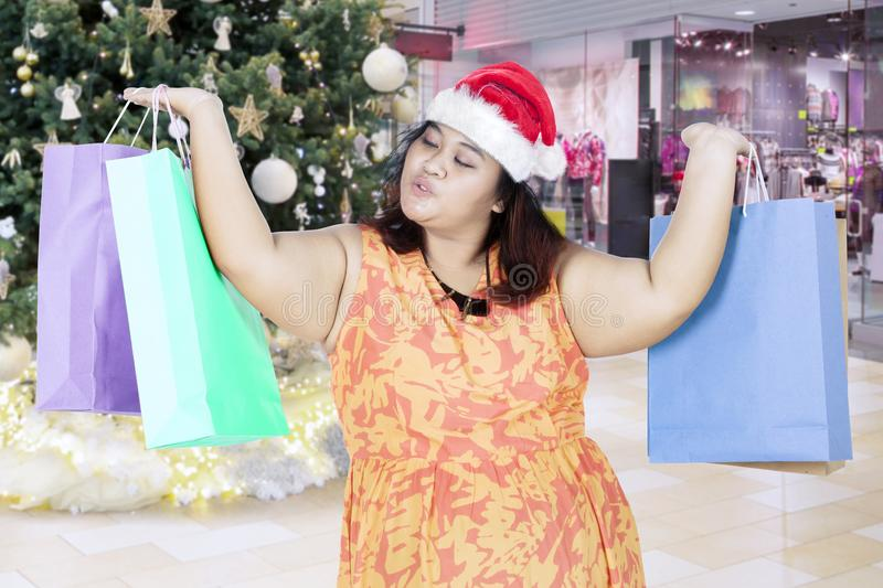Overweight woman lifting Christmas gifts in the mall royalty free stock photography