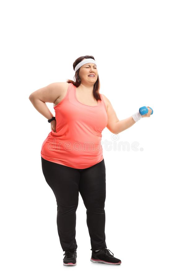 Overweight woman lifting a small dumbbell and experiencing back. Full length portrait of an overweight woman lifting a small dumbbell and experiencing back pain stock photo