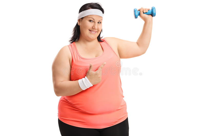 Overweight woman lifting a small dumbbell and pointing. Isolated on white background royalty free stock images