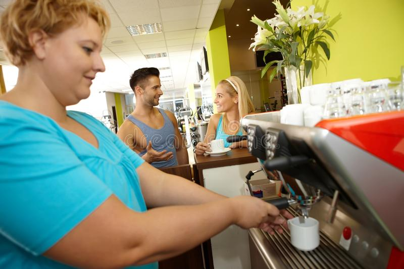 Overweight woman making coffee in gym stock image