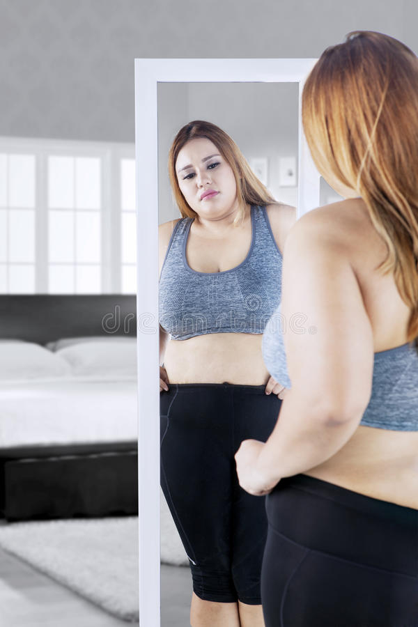 Overweight woman with mirror in bedroom stock photography