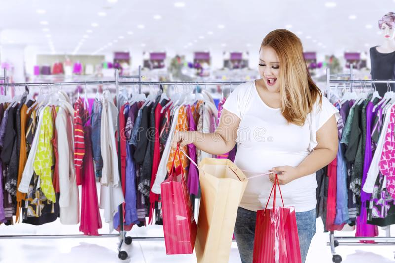 Overweight woman opening her shopping bag stock photo