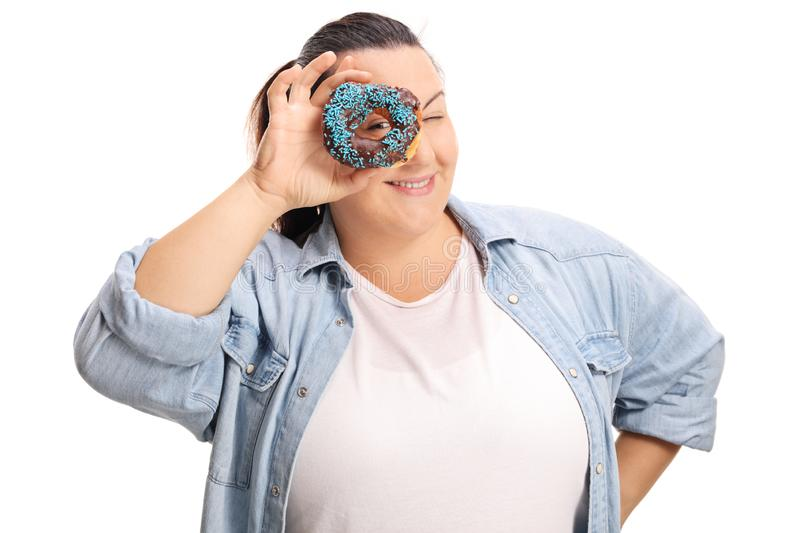 Overweight woman peeking thrugh a chocolate donut. Isolated on white background royalty free stock photos