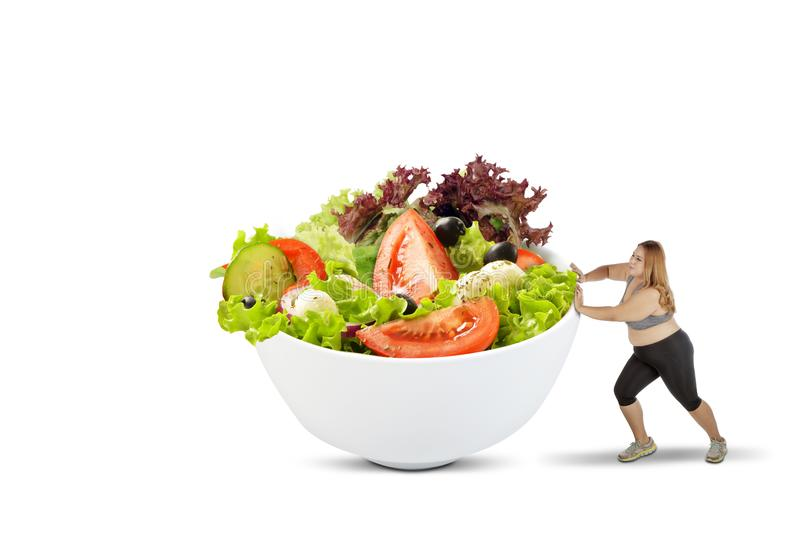 Overweight woman pushing a bowl of salad stock image