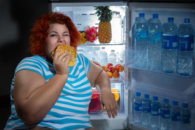 Overweight woman with refrigerator. Photo at night of Overweight woman opening refrigerator and looking for a late supper royalty free stock photo