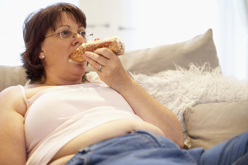 Overweight Woman Relaxing On Sofa stock images