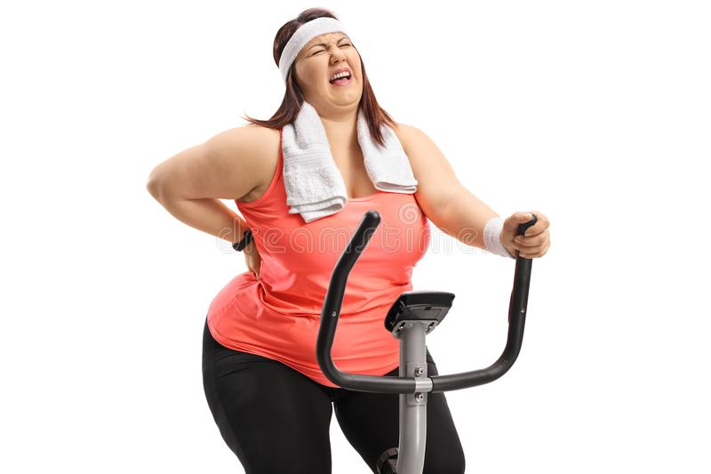 Overweight woman riding an exercise bike and experiencing back p. Ain isolated on white background stock photography