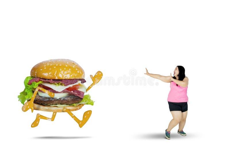 Overweight woman runs away from a hamburger stock photos