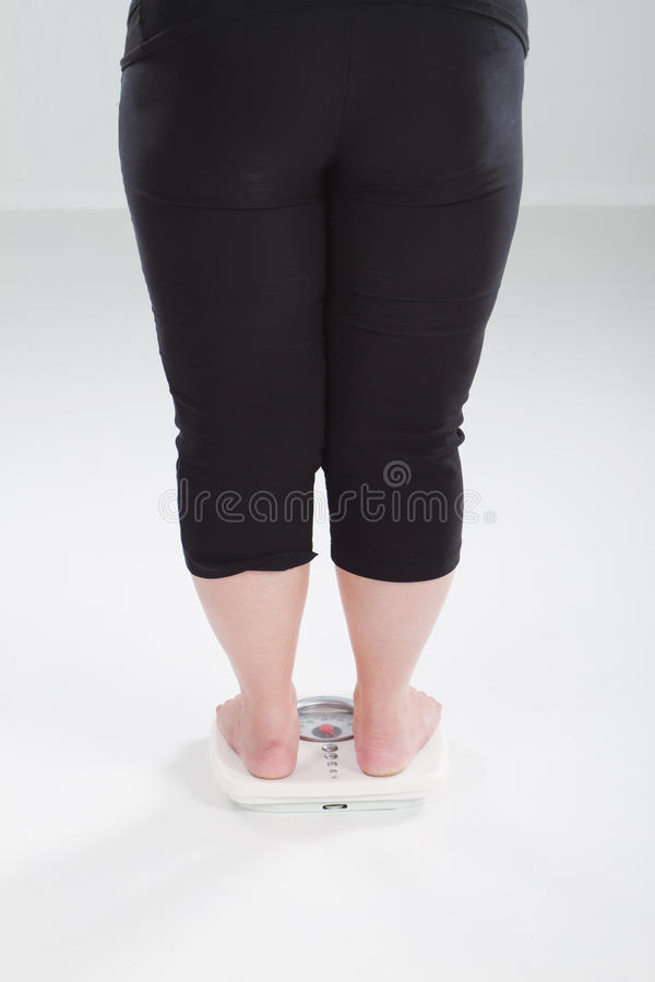 Overweight woman on scale royalty free stock photos