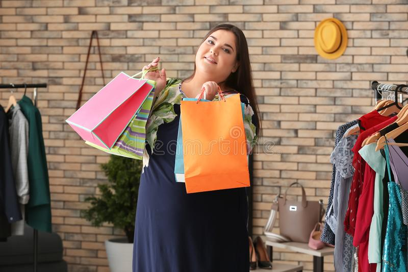 Overweight woman with shopping bags in clothing store stock photography