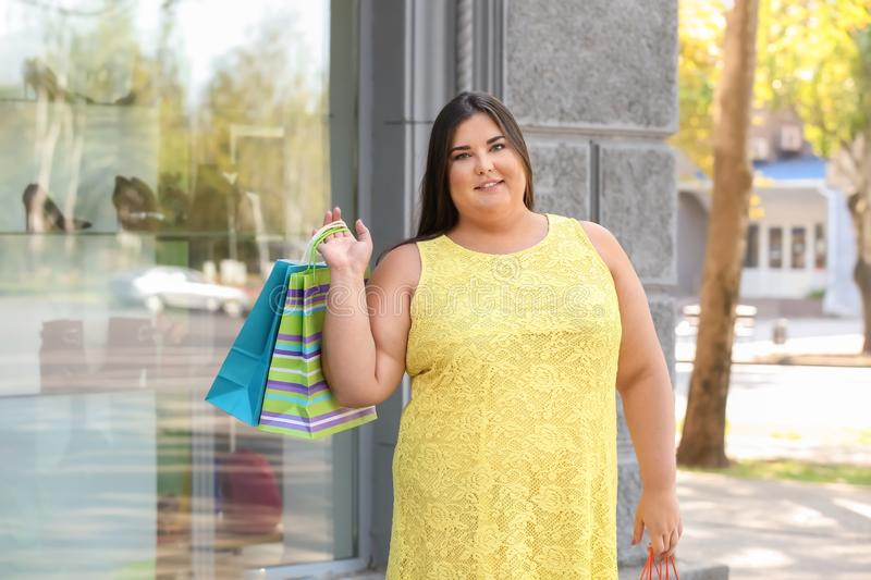 Overweight woman with shopping bags near clothing store on city street royalty free stock images