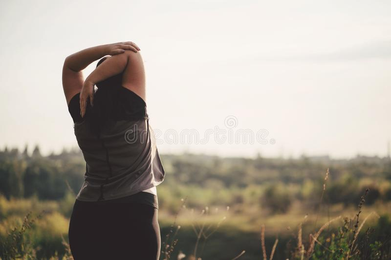 Overweight woman stretching hands during walk royalty free stock image