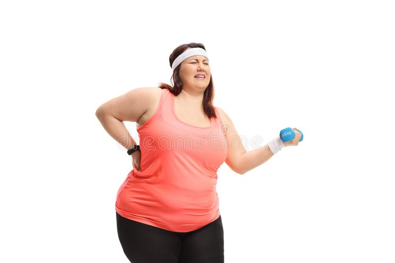 Overweight woman strugling to lift a small dumbbell. Isolated on white background royalty free stock photography