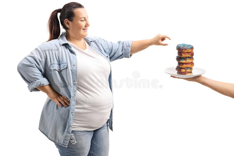 Overweight woman taking a donut. Isolated on white background royalty free stock photography
