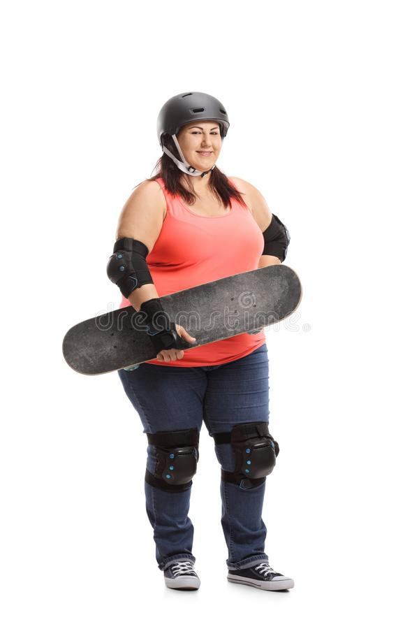 Overweight woman wearing protective gear holding a skateboard. Full length portrait of an overweight woman wearing protective gear holding a skateboard isolated stock photography