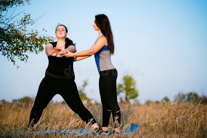 Overweight woman working out with personal trainer. Overweight woman with personal trainer doing lateral lunges. Fitness, sport, weight loss, training, teamwork royalty free stock photography