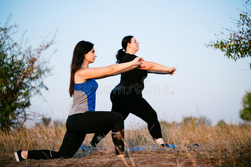 Overweight woman working out with personal trainer. Overweight women working out with personal trainer. Individual training outdoors. Fitness, sport, training stock photo