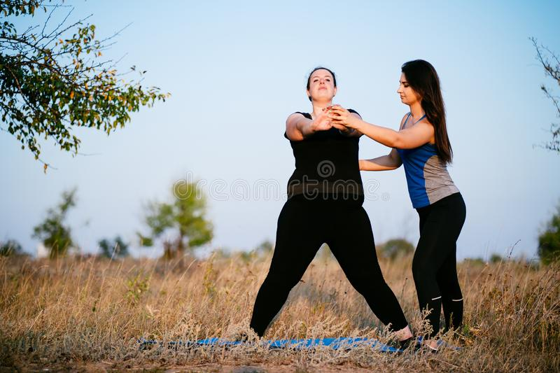 Overweight woman working out with personal trainer. Overweight women with personal trainer doing lateral lunges. Fitness, sport, weight loss, training, teamwork royalty free stock photography