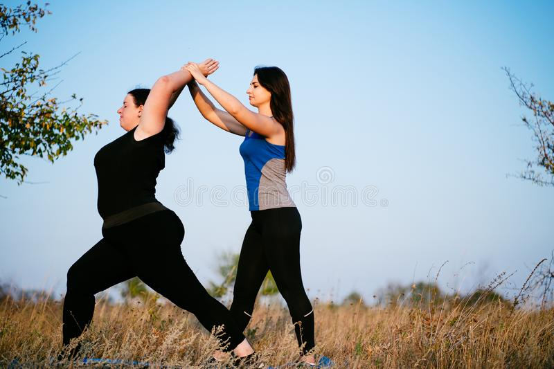 Overweight woman working out with personal trainer. Overweight women doing lunges exercise with trainer support. Personal fitness instructor controlling his royalty free stock photos
