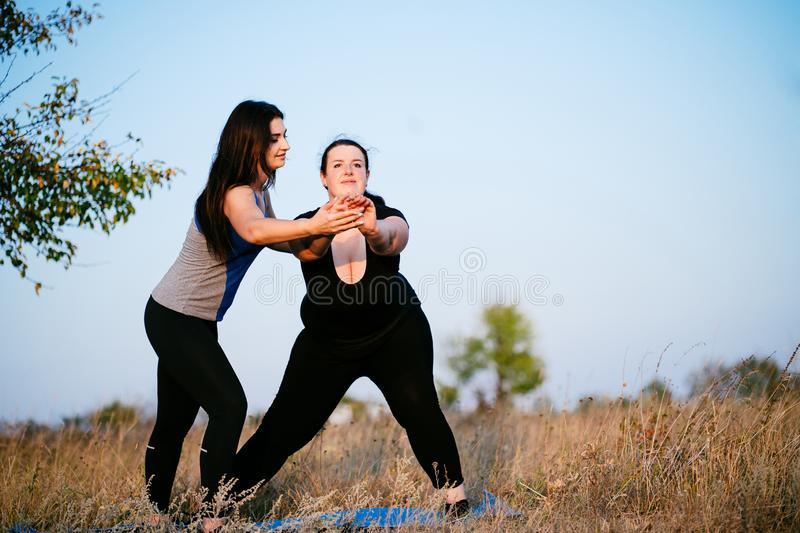 Overweight woman working out with personal trainer. Overweight women with personal trainer doing lateral lunges. Fitness, sport, weight loss, training, teamwork royalty free stock images