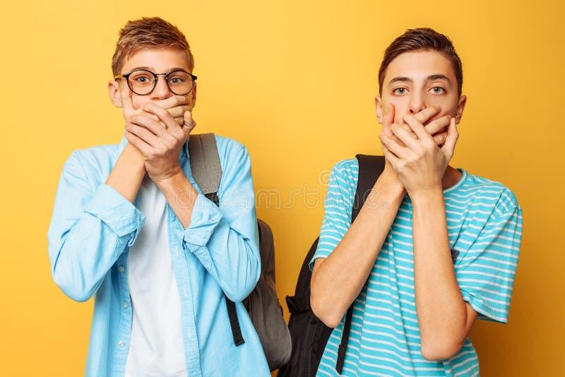 Overweldigd, geschokt, versperren twee kerels, tieners met vrees, behandelen hun monden met beide handen, op een gele achtergrond stock foto's