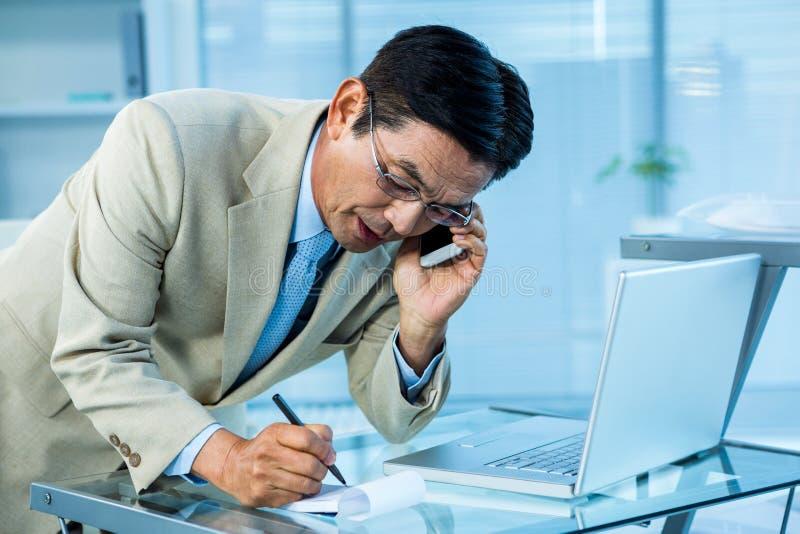 Overweldigde Aziatische zakenman die de telefoon en het schrijven beantwoordt royalty-vrije stock foto's