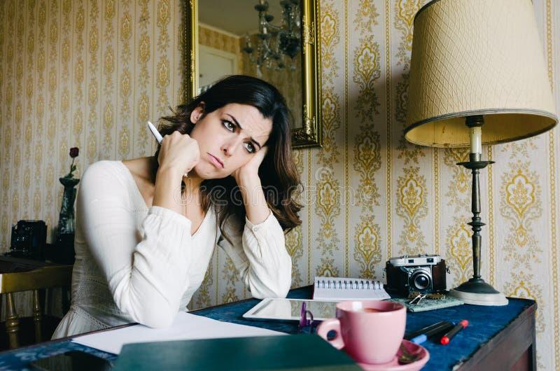 Overweldigde jonge vrouw die thuis werken stock afbeelding