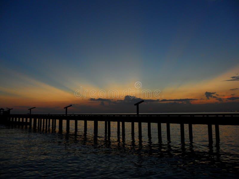 Overweldigen oranjegeel na gloed op donkerblauwe zonsonderganghemel over de brug aan het overzees stock afbeelding