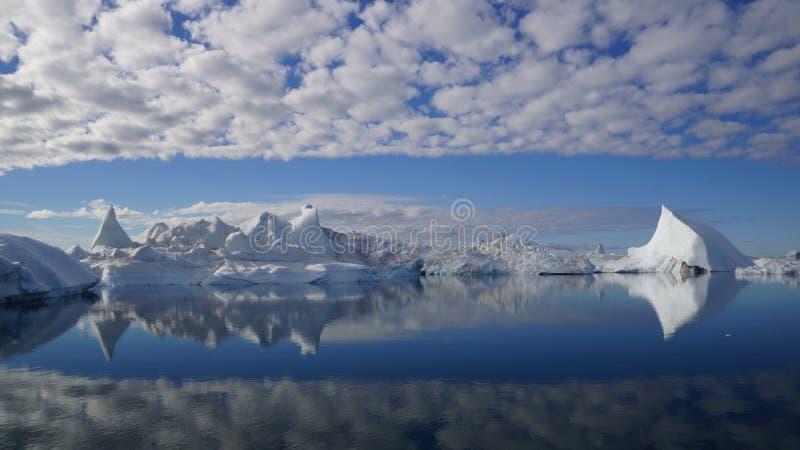 Overweldigend effect van ijsbergen en wolken die in het water nadenken stock foto's