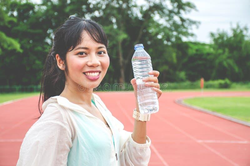 Overweldigende geschiktheidsvrouw die een fles water na Jogging houden in openlucht bij het stadion in zonnige ochtend, Lege ruim royalty-vrije stock fotografie