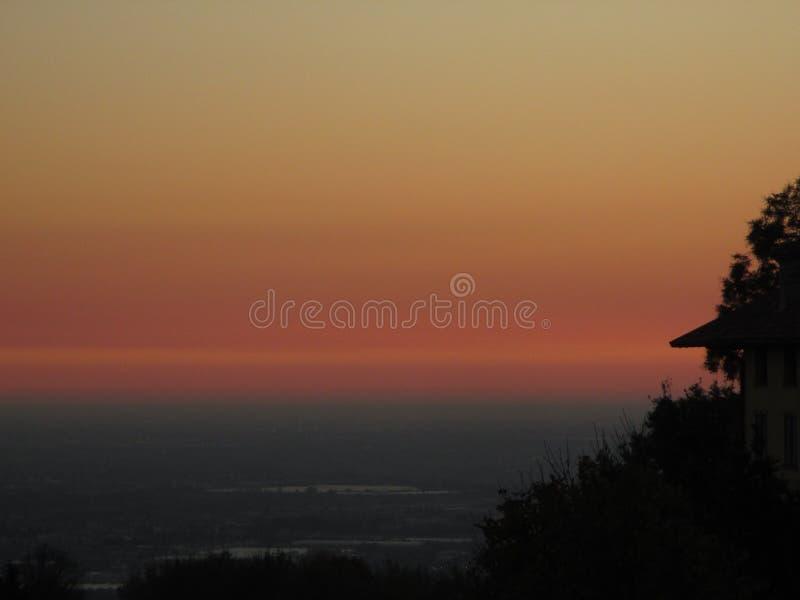 Overweldigende gradatie van pastelkleur geel en roze van de latere zonsonderganghemel, Bergamo royalty-vrije stock fotografie
