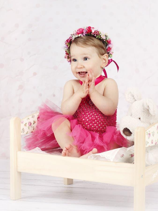 Overweldigende meisjezitting op het bed met bloemenkroon royalty-vrije stock afbeelding