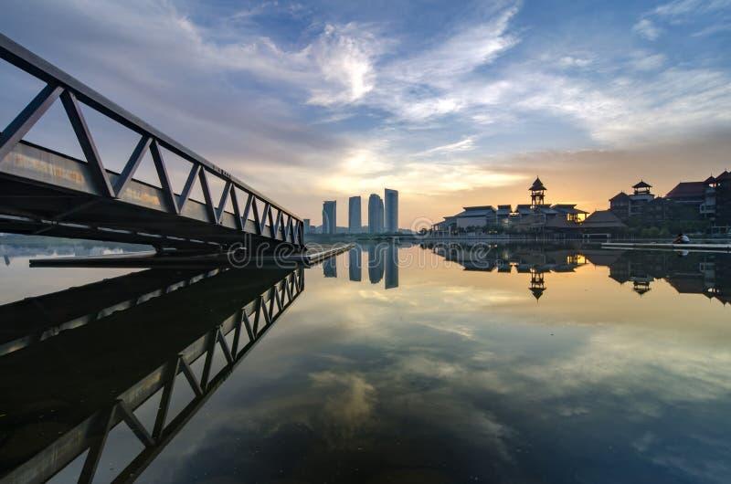 Overweldigende ochtendmening dichtbij de oever van het meer, het moderne gebouw en de houten pier stock afbeeldingen