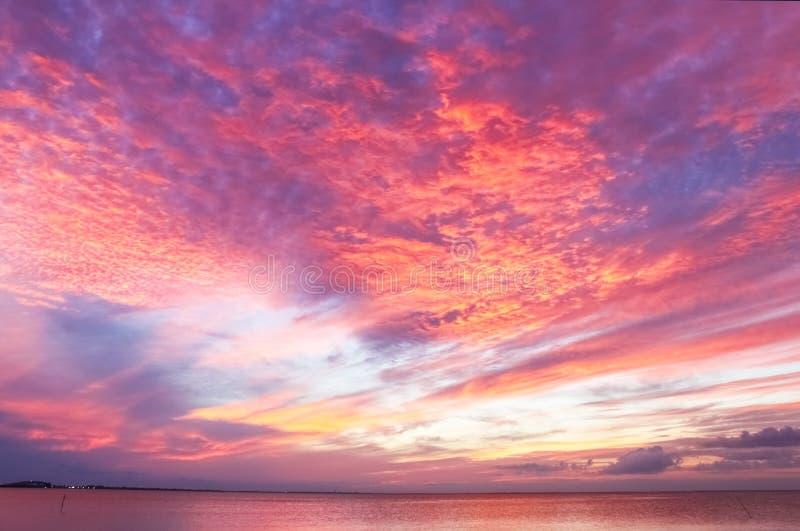 Overweldigende rode en purpere en gele zonsondergang die de oceaan overdenken royalty-vrije stock fotografie