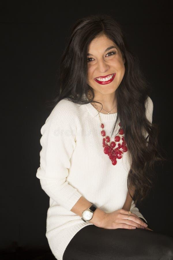 Overweldigende schoonheids vrouwelijke modelzitting die zwarte achtergrond glimlachen stock foto's