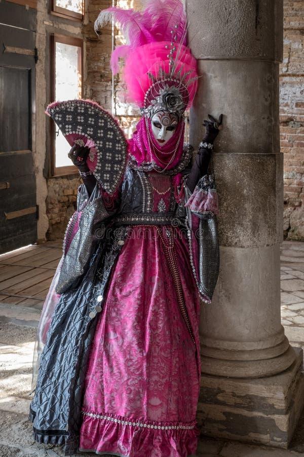 Overweldigende vrouw in kleurrijk roze kostuum en overladen masker in Venetië Carnaval royalty-vrije stock foto's