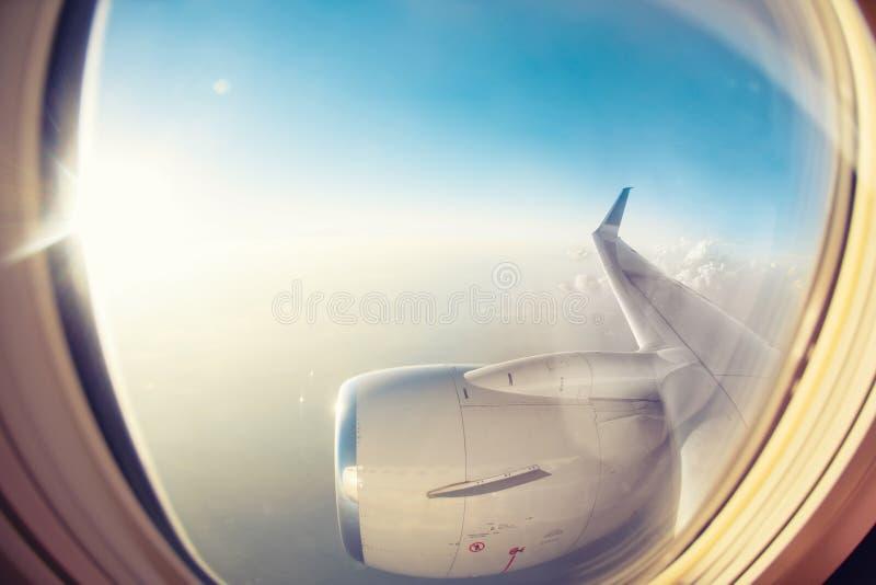 Overweldigende zonsopgangmening over een hoge hoogte van het passagiersvenster van een conventioneel vliegtuig De kleuren van de  stock afbeelding