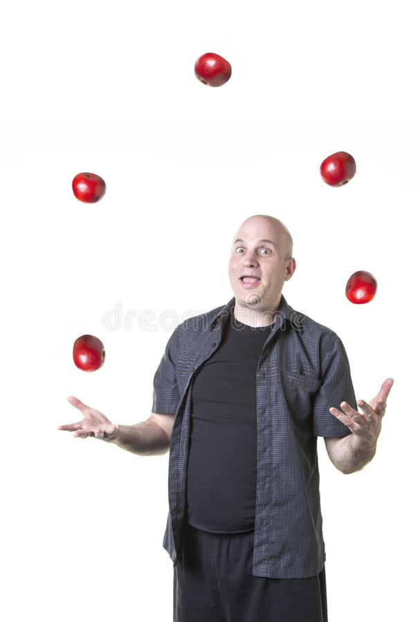 Overwelmed man juggling too many things. A man trying to juggle too many apples stock photos